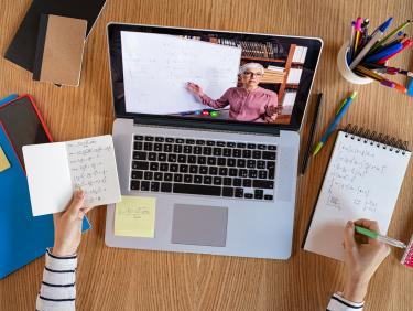 Hochwinkelaufnahme einer Videokonferenz mit Lehrender auf Laptop.