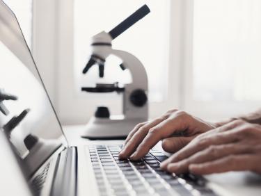 Person arbeitet an einem Laptop mit Mikroskop im Hintergrund